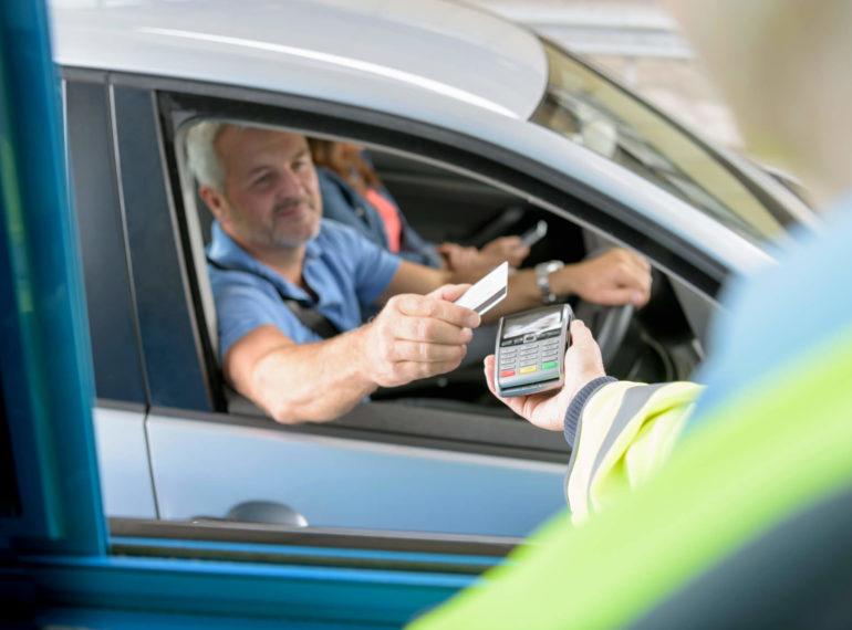 Homem usando cartão de dentro do carro
