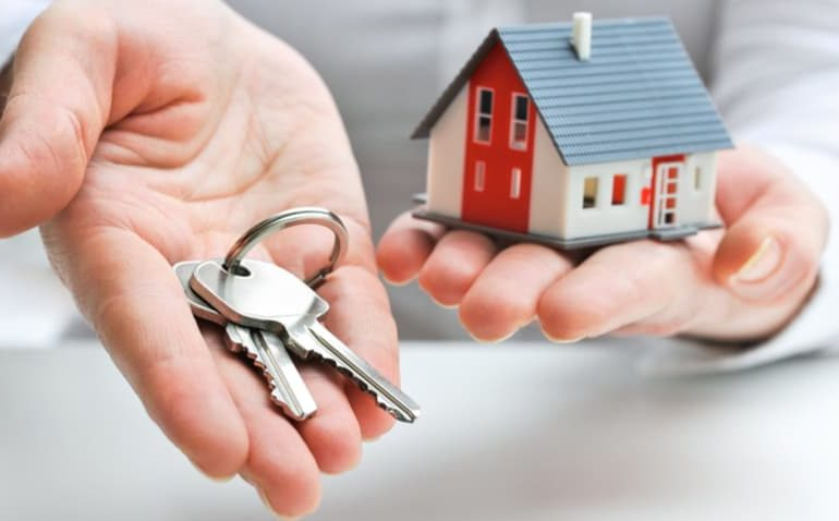mão oferecendo uma chave e uma casa