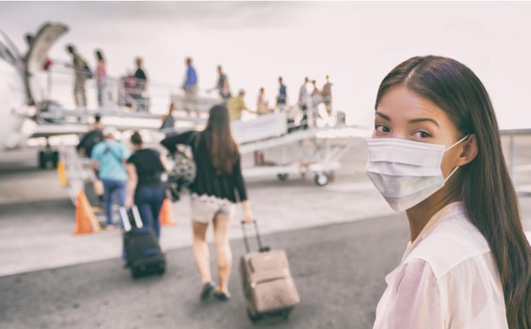 mulher com máscara embarcando em um aviao