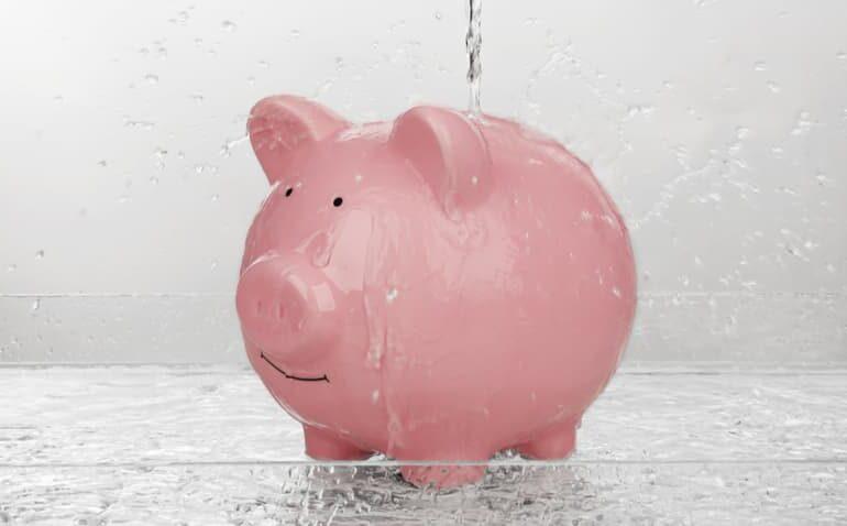 Porta-moeda em formato de porquinho embaixo de um esguicho de água